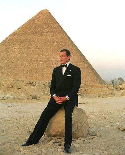 In this file photo, former secret agent 007 Roger Moore poses in front of Cheops, the largest of Egypt's three Pyramids on the Giza plateau south of Cairo, on 2 July 1999. Moore, 72, was in Egypt to promote the country's tourist attractions after a bloody attack on foreign tourists in Luxor in 1997 left the industry in tatters. The ex-James Bond was no stranger to Egypt, where he shot 22 years ago the famous thriller The Spy Who Loved Me. | AFP