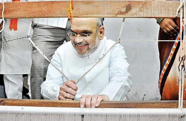 BJP national president Amit Shah tries his hand at a handloom weaving unit in Nalgonda on Monday| Express photo
