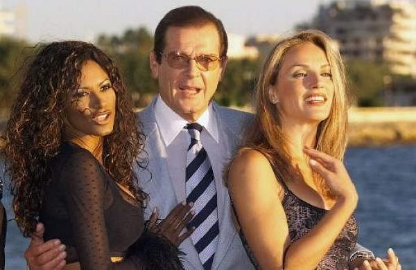 This file photograph taken on October 5, 1999 shows  British actor Roger Moore (C) posing with actresses Traci Bingham (L) et Eva Halina in Cannes. | AFP