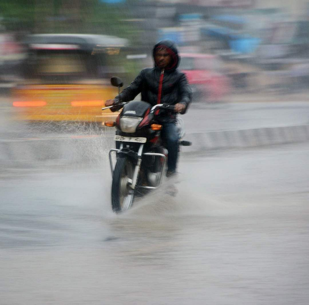 Man driving a motorcycle during heavy rain at Sangareddy district, Telangana.