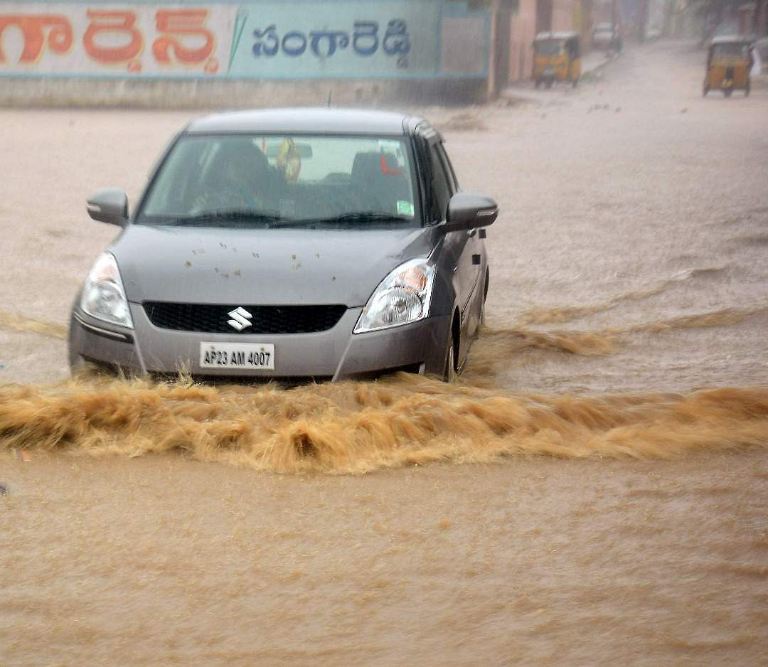 A driver tries to maneuver his car through a flooded road during the heavy rain at Sangareddy district, Telangana.