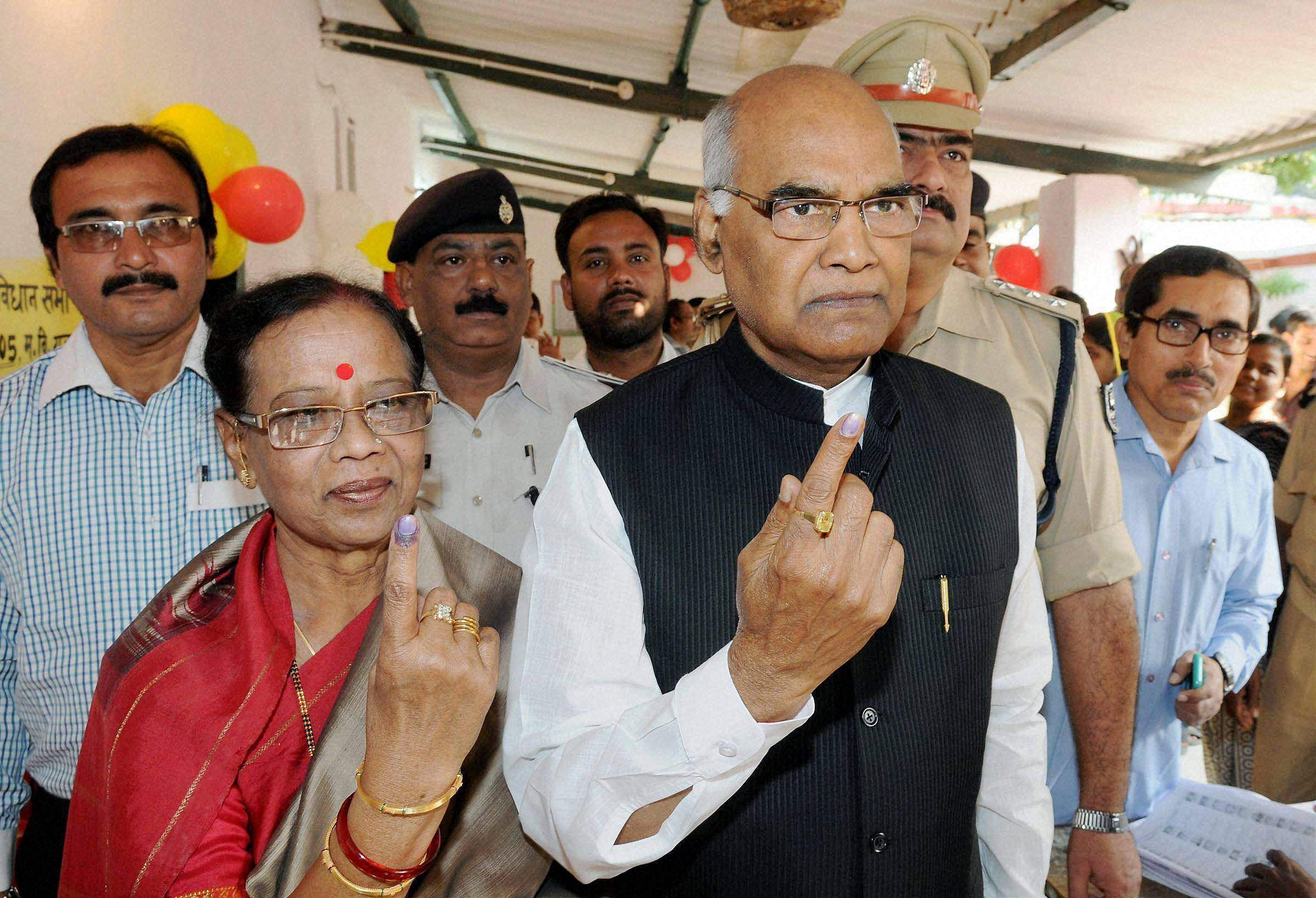 Bihar Governor Ram Nath Kovind with his wife shows their inked finger after casting vote during third phase of Bihar assembly elections, in Patna.