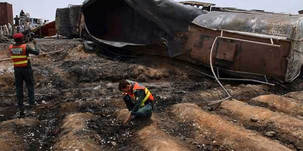 Pakistani rescue workers examine the site of an oil tanker explosion at a highway near Bahawalpur, Pakistan, Sunday, June 25, 2017 | AP