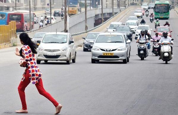 A woman dangerously crosses a busy road  at Kadubeesanahalli. | (Pushkar V | Express Photo Service)