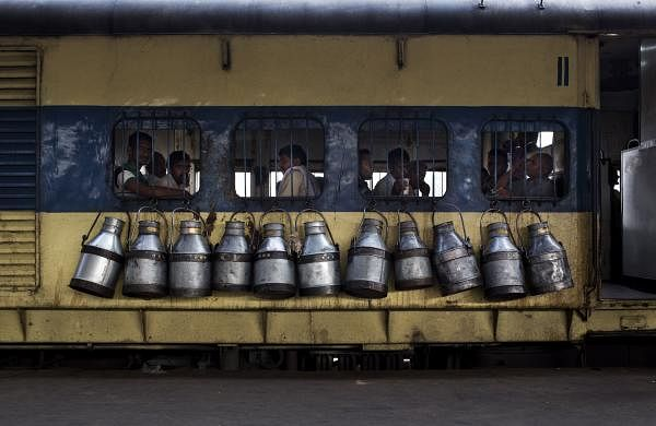 Empty milk canisters hang from a train belonging to milkmen | AP