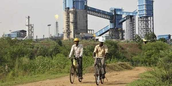Men ride their bicycles in front of the Bhushan Steel plant in Odisha. (File photo | Reuters)