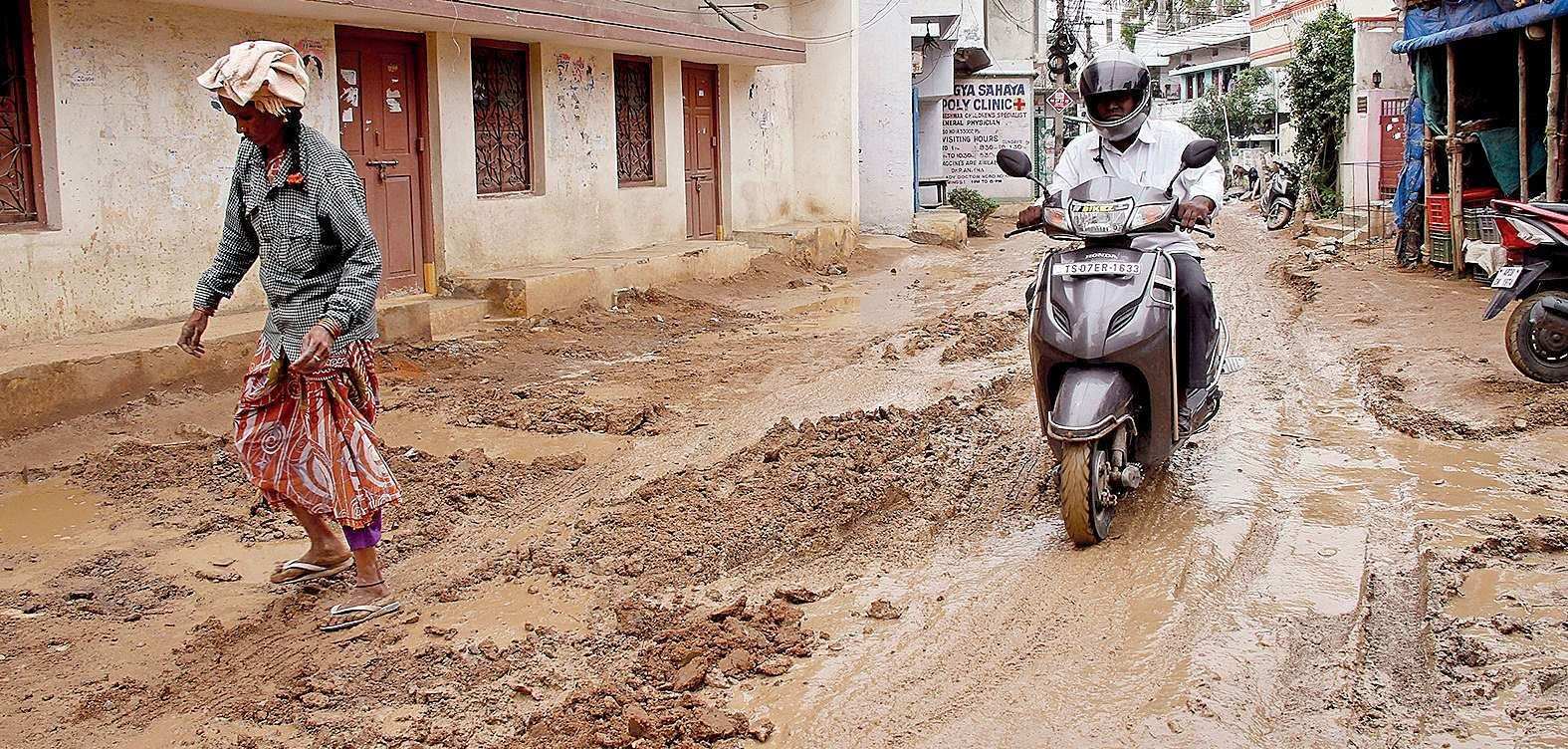 Woman walks through sludge while a motorist rides carefully out of fear of skidding in Kukatpally| Express photo