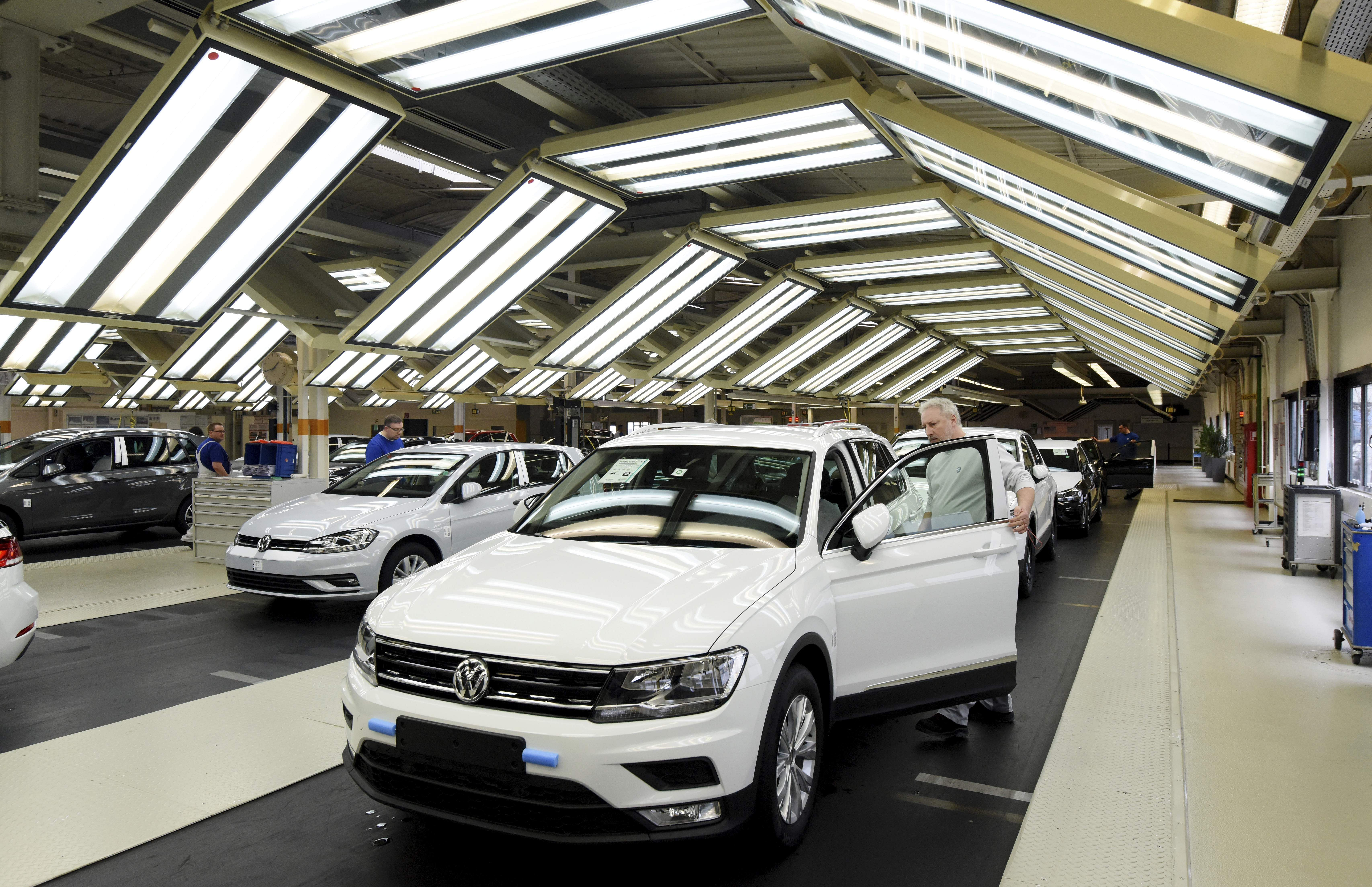 Employees work at the production line of a volkswagen plant file photo ap