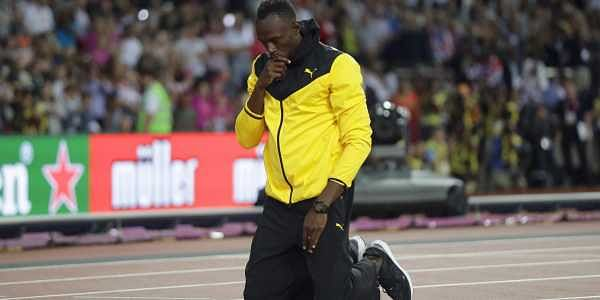 Jamaica's Usain Bolt kneels down during a lap of honor at the end of the World Athletics Championships in London Sunday, Aug. 13, 2017. | AP