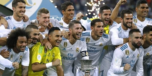 Real Madrid's players celebrate with their trophy after winning the Spanish Super Cup against Barcelona at the Santiago Bernabeu Stadium. | AP