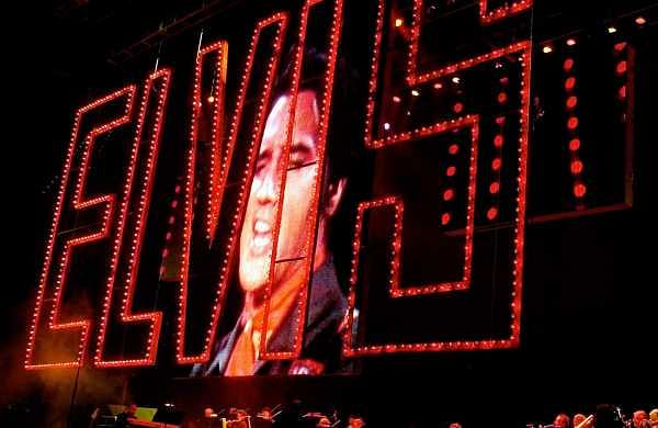 This Aug. 16, 2002 file photo shows an image of Elvis Presley singing as his band plays below at the start of the Elvis Presley 25th Anniversary Concert in Memphis, Tenn.