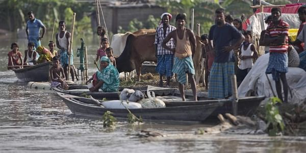 Flood affected villagers wait for relief in Pokoria village of north eastern Assam. (Photo | AP)