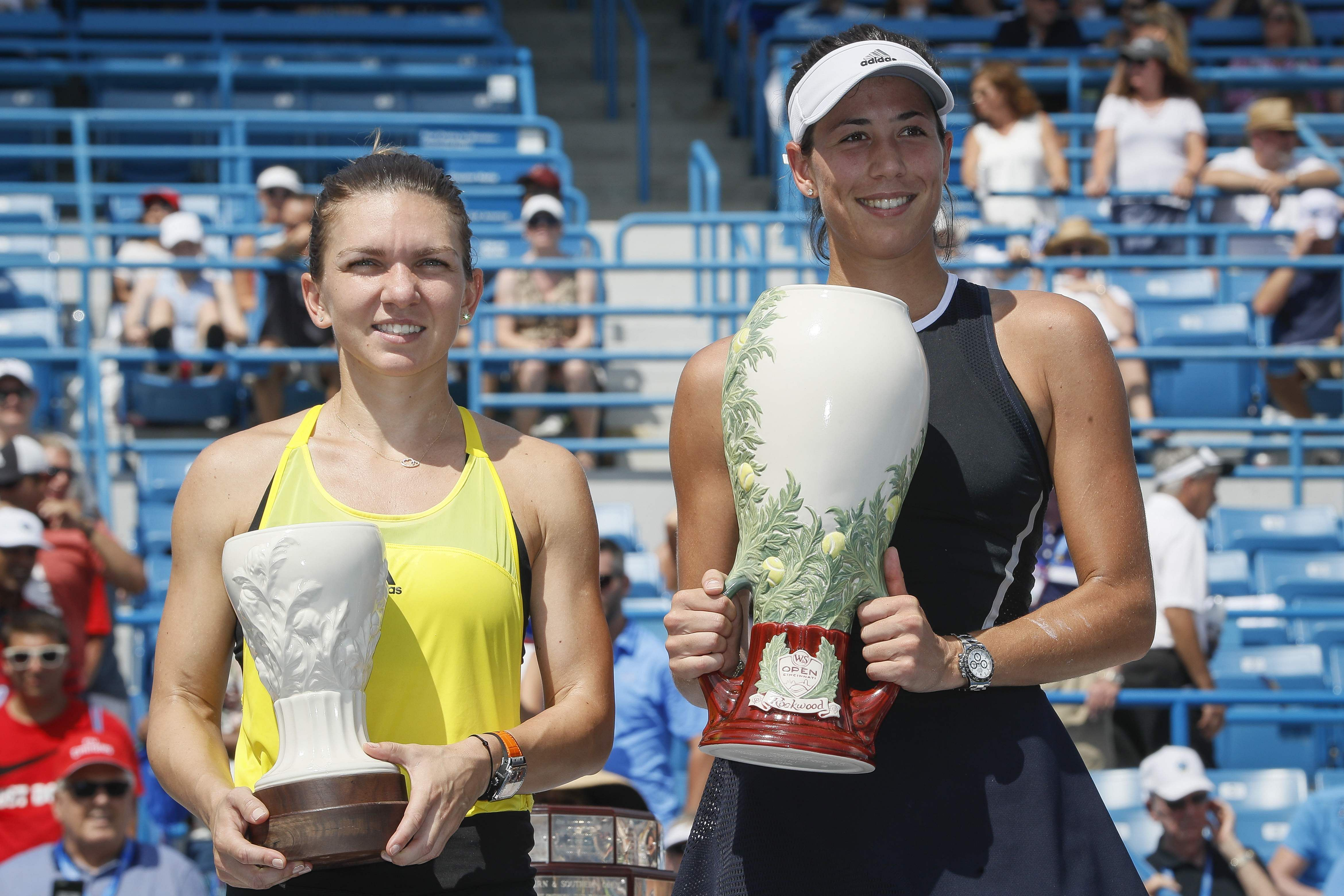 Garbine Muguruza, of Spain, right, holds the Rookwood Cup after defeating Simona Halep, of Romania, left, during the women's singles final at the Cincinnati Masters. | AP