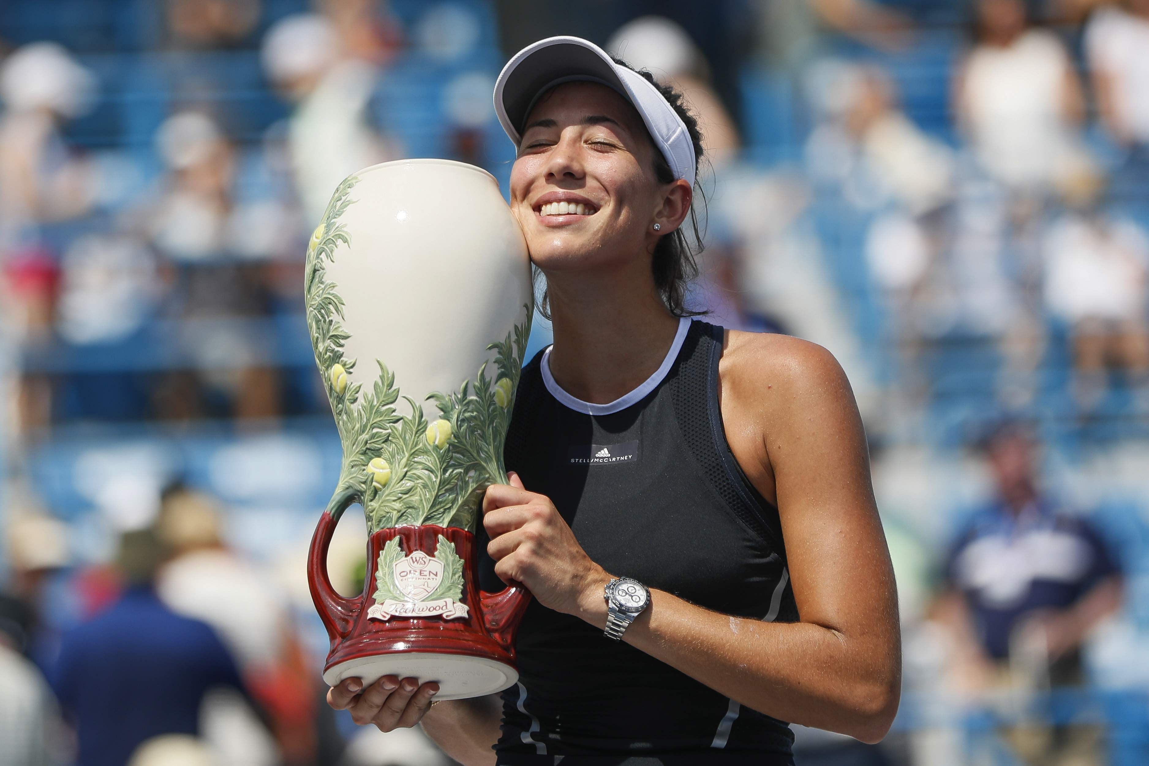 Garbine Muguruza, of Spain, holds the Rookwood Cup after defeating Simona Halep, of Romania, in the women's singles final at the Cincinnati Masters. | AP