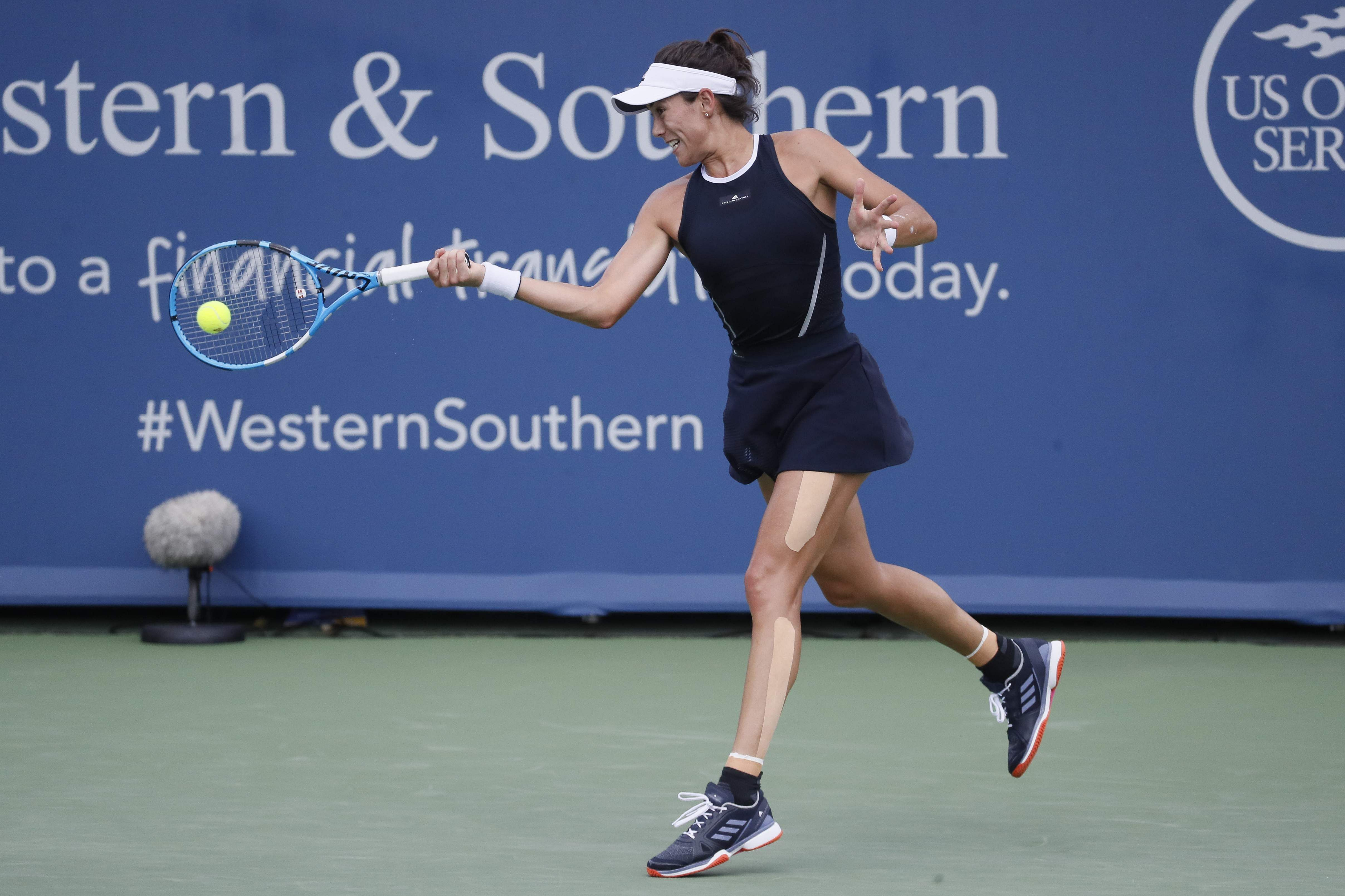 Garbine Muguruza, of Spain, returns to Simona Halep, of Romania, during the women's singles final at the Western and Southern Open. | AP