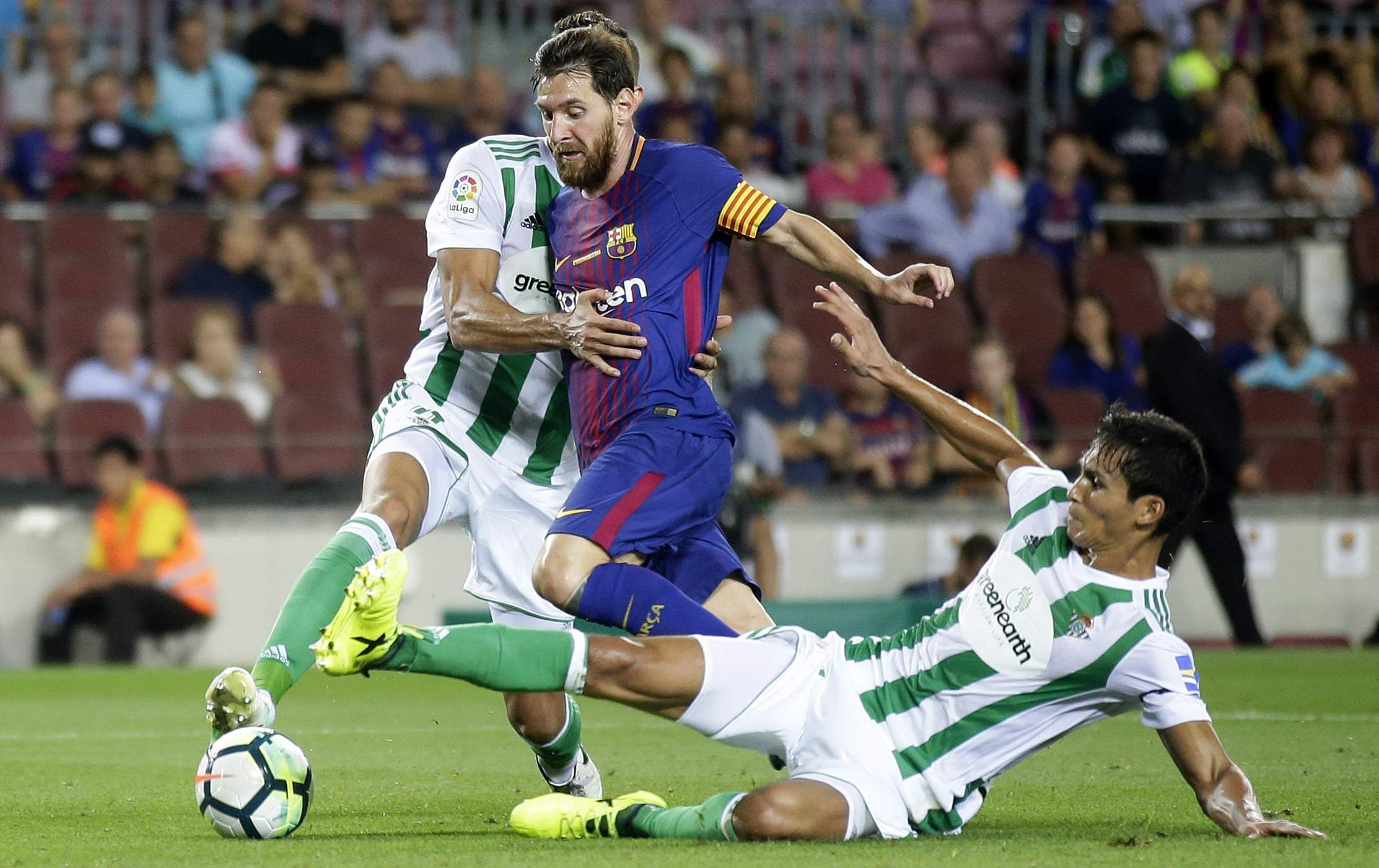 FC Barcelona's Lionel Messi, center, duels for the ball against Betis' Aissa Mandi, right, during the Spanish La Liga soccer match between FC Barcelona and Betis. | AP