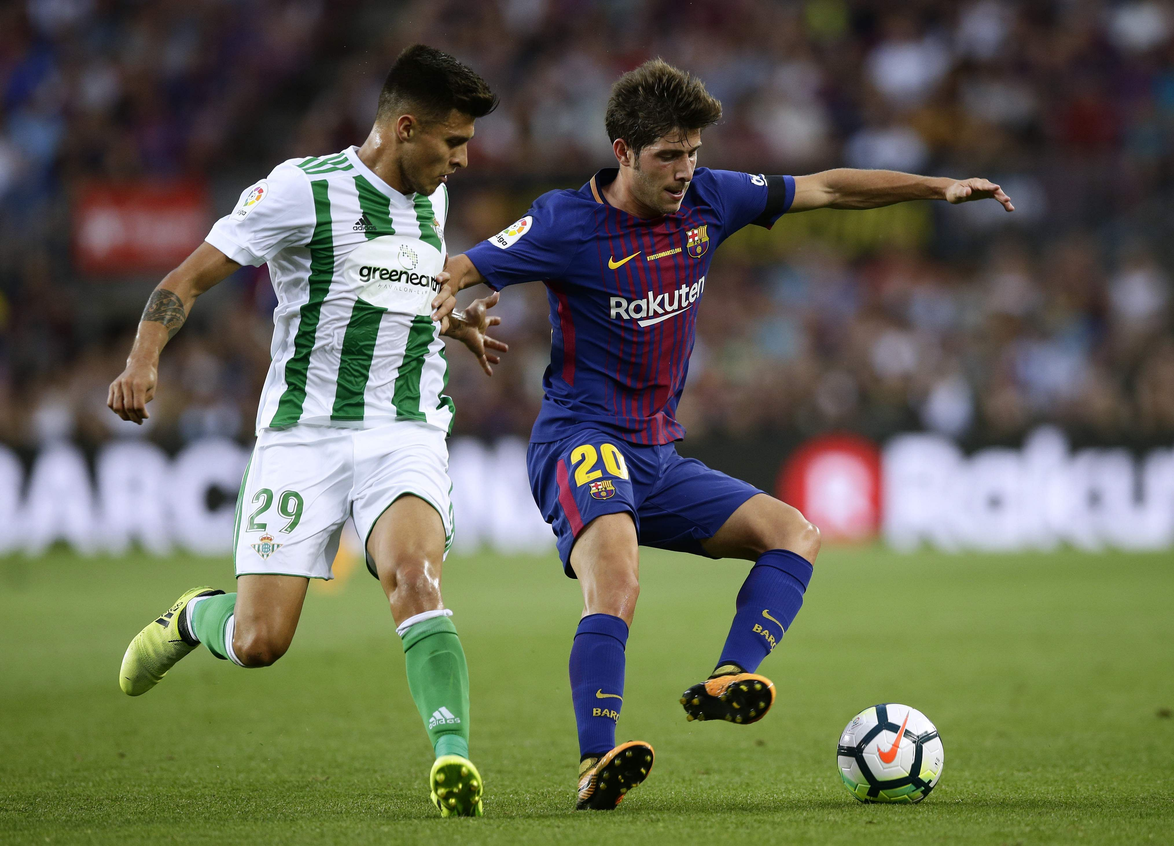 FC Barcelona's Sergi Roberto, right, duels for the ball against Betis' Juanjo Narvaez during the Spanish La Liga soccer match between FC Barcelona and Betis at the Camp Nou stadium. | AP