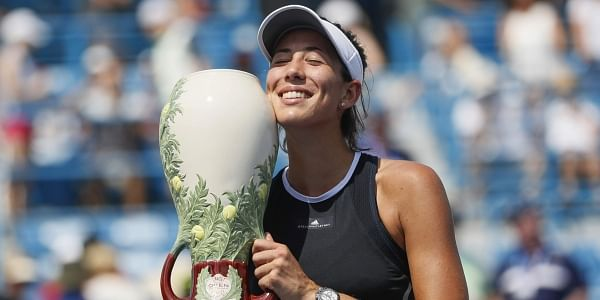 Garbine Muguruza, of Spain, holds the Rookwood Cup after defeating Simona Halep, of Romania, in the women's singles final at the Western and Southern Open. | AP
