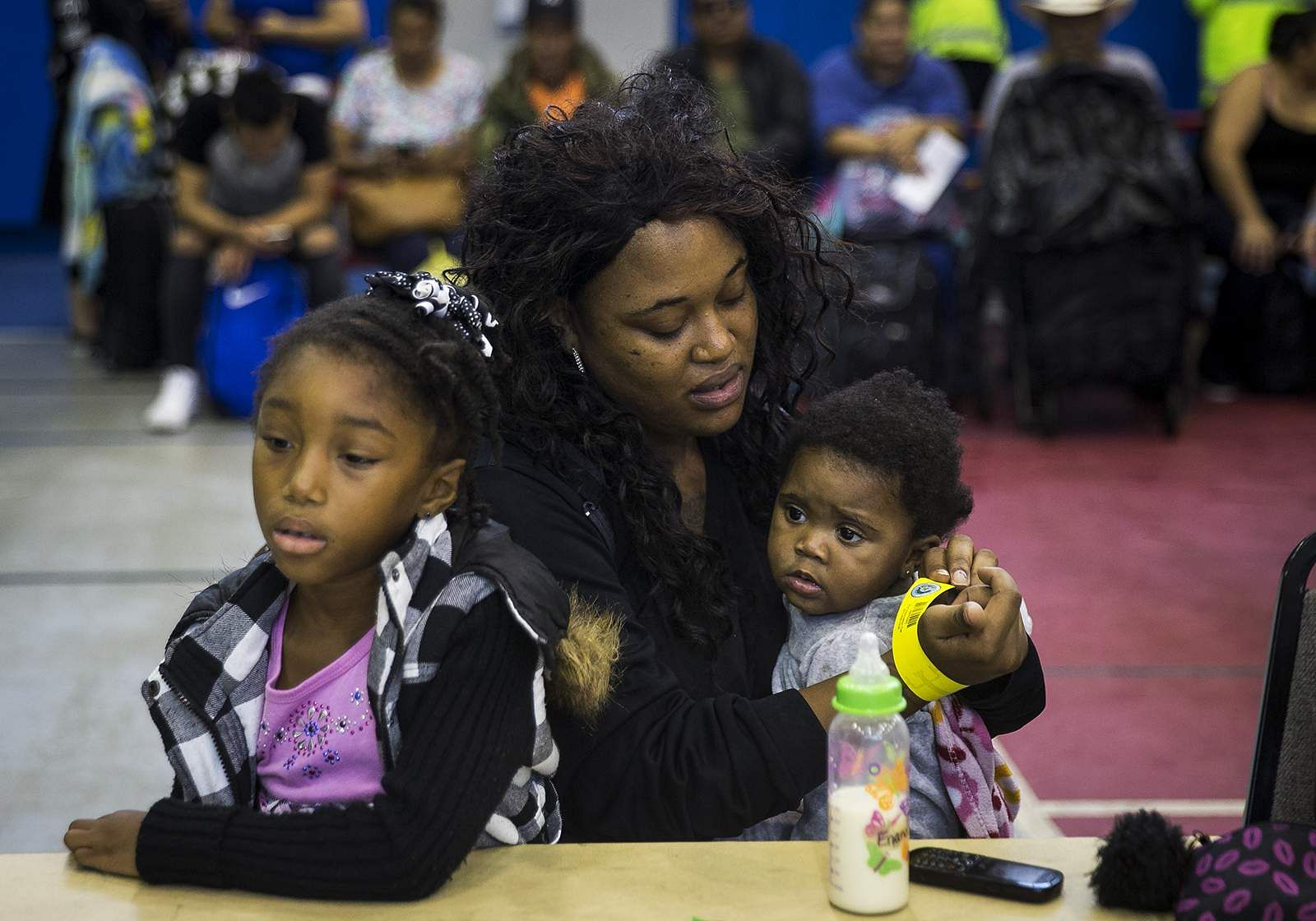 A women secures an identification wristband to herself while holding her daughters, as they wait to board a bus headed for San Antonio at an evacuation ...