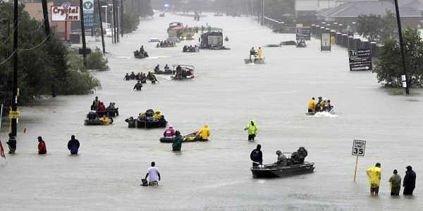 Rescue boats fill a flooded street as flood victims are evacuated as floodwaters from Tropical Storm Harvey rise. (AP)