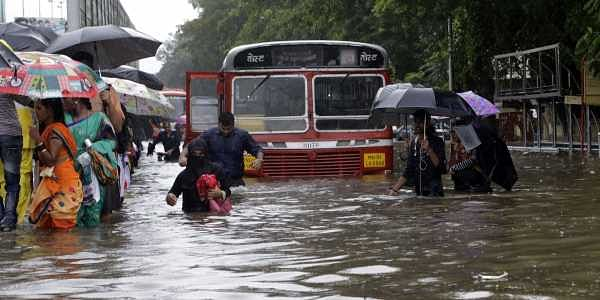 People wade through a waterlogged street. Heavy rains Tuesday brought Mumbai to a halt flooding vast areas of the city.  (Photo | AP)