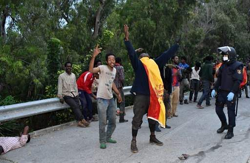 Migrants run through Spain-Morocco border post