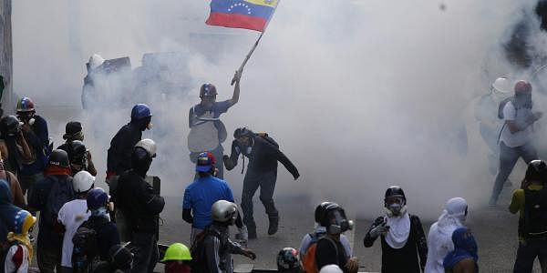 A protester holds up a Venezuelan flag amid tear gas fired by security forces in Caracas, Venezuela, Friday, May 26, 2017. Anti-government demonstrators took to the streets in an attempt to spur the armed forces into putting a brake on the repression of protesters. (AP Photo/Ariana Cubillos)