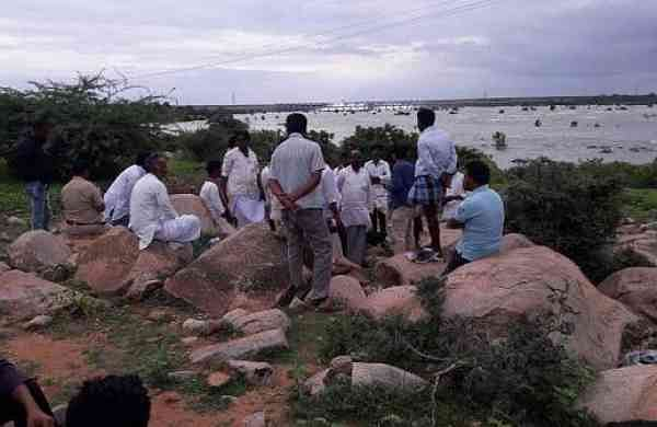 Villagers sit on the banks of the Krishna river waiting for the rescue operation to begin. (Photo | EPS)