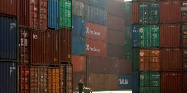 A woman walks past containers at a port in Shanghai. | REUTERS