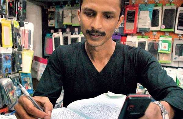 Sabin, who runs a mobile recharge outlet in Kaloor, says the number of daily customers coming for recharging has gone down sharply from around 200 to 50 | K Shijith