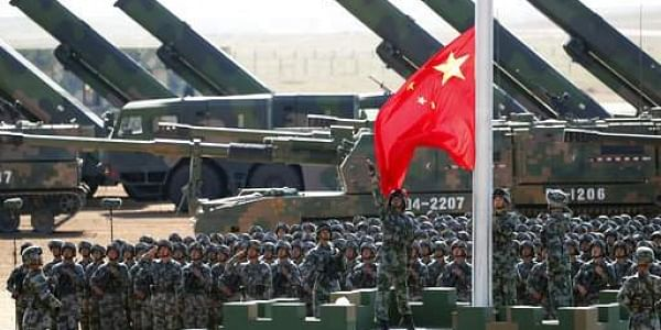 In this July 30, 2017 photo released by China's Xinhua News Agency, Chinese People's Liberation Army (PLA) troops perform a flag raising ceremony for a military parade to commemorate the 90th anniversary of the founding of the PLA on August 1 at Zhurihe t
