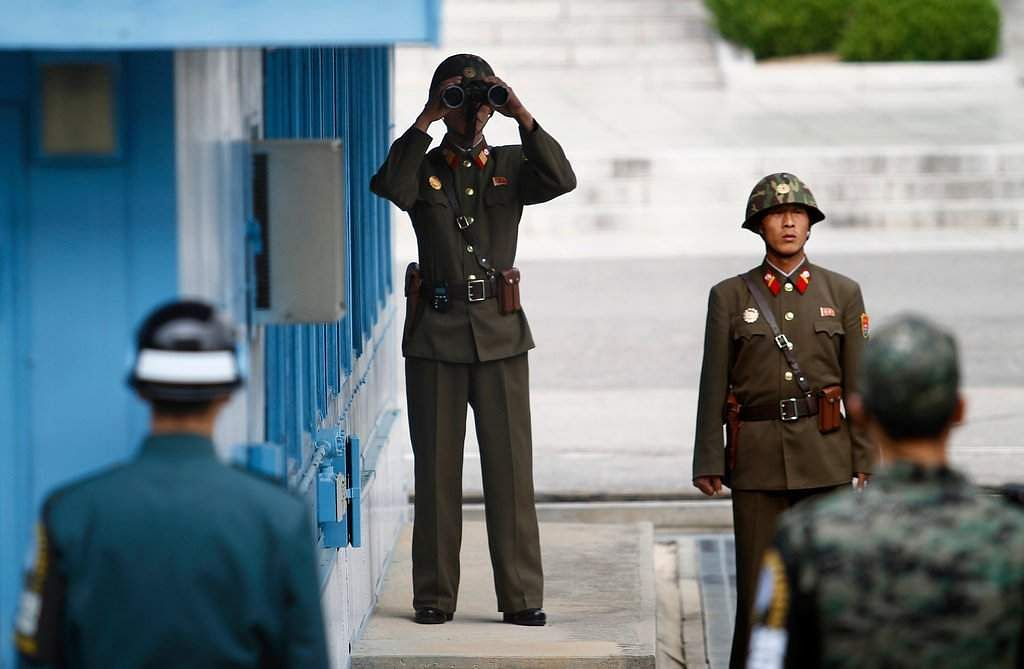 Soldiers from North Korea center and South Korea at Panmunjom a border village