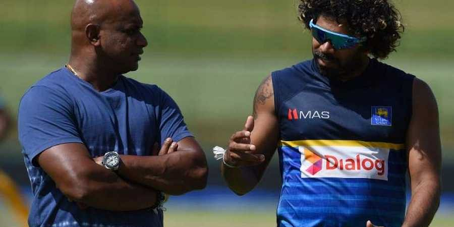 Sri Lankan cricketer Lasith Malinga (L) speaks with chairman of selectors Sanath Jayasuriya during a practice session at the Pallekele International Cricket Stadium in Pallekele.|AFP