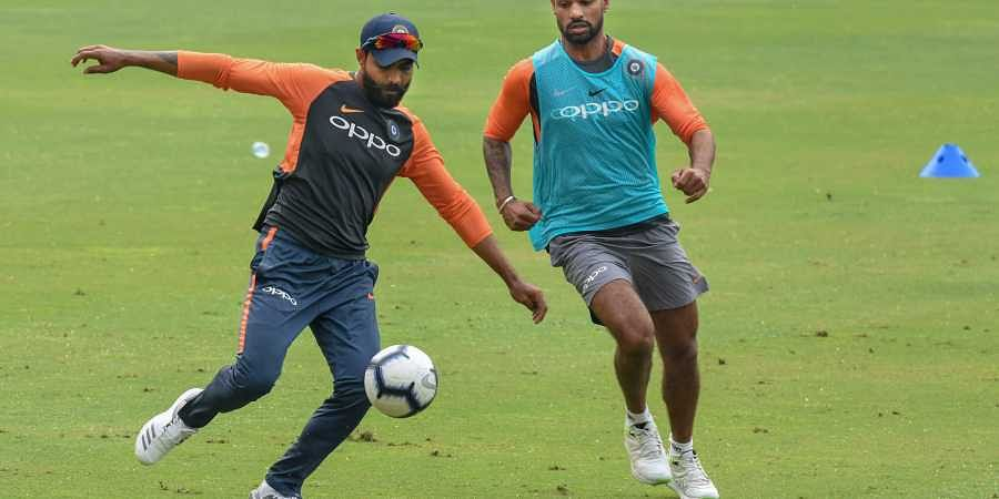 Indian cricketers Shikhar Dhawan and Ravindra Jadeja play football during a practice session ahead of the first One Day International cricket match against West Indies at ACA Cricket Stadium Barsapara in Guwahati. (Photo | PTI)