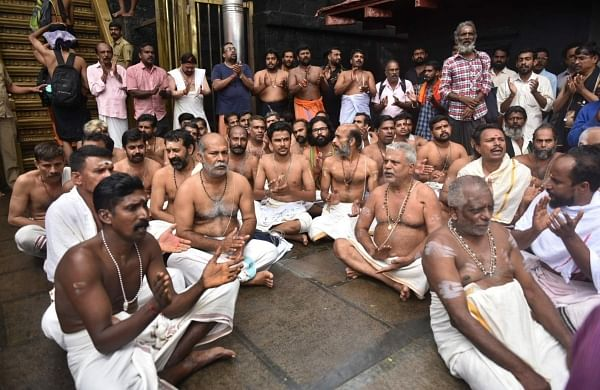 Hindu priests and temple staff sit on a protest against a ruling from India's top court to let women of menstruating age entering Sabarimala temple, one of the world's largest Hindu pilgrimage sites, in the southern Indian state of Kerala, Friday, October 19, 2018. | AP