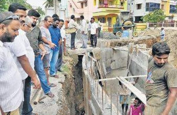 Residents look on as workers dig up Sethunaryanan street. | Express Photo Services