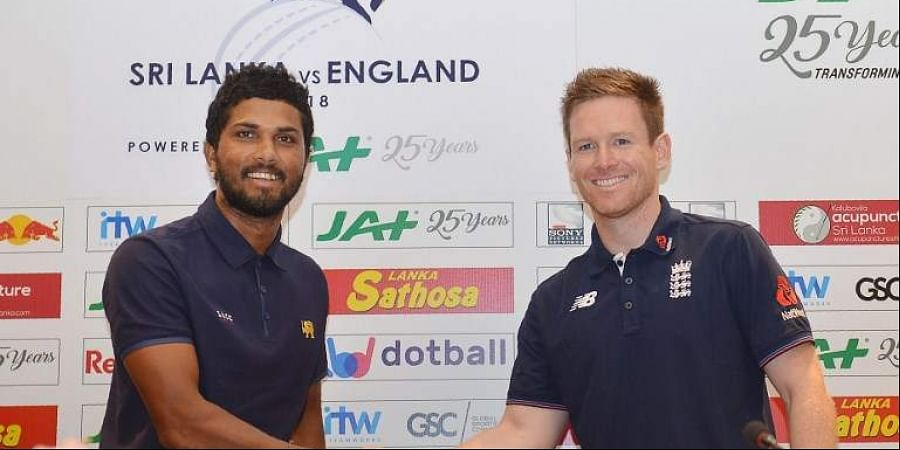 Sri Lankan cricket team captain Dinesh Chandimal (L) and England cricket captain Eoin Morgan shake hands as they pose for photographers at a press conference in Colombo. (Photo | AFP)