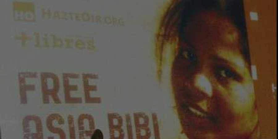 Ashiq Masih, husband of Asia Bibi, a Christian woman facing death sentence for blasphemy, points to a poster bearing an image of his wife Asia at a living area in Lahore.(File|AFP)