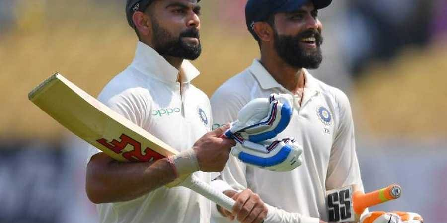 India's captain Virat Kohli (L) and teammate Ravindra Jadeja walk back to the pavillion during the second day's play of the first Test cricket match between India and West Indies at the Saurashtra Cricket Association stadium in Rajkot. (Photo | AFP)