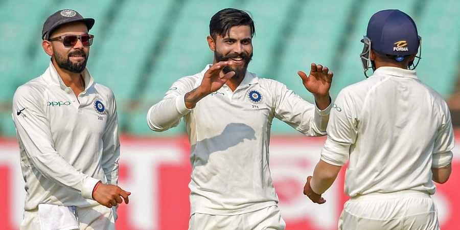 Indian bowler Ravindra Jadeja C celebrates the wicket of West Indies batsman Sunil Ambris as team captain Virat Kohli L looks on during their first test cricket match in Rajkot. (Photo   PTI)