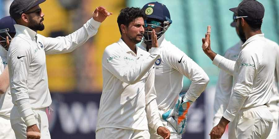 Indian bowler Kuldeep Yadav with his teammates celebrates the wicket of West Indies batsman Shai Hope during their first test cricket match in Rajkot. (Photo | PTI)