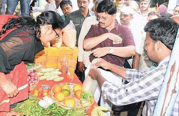 District Collector B Lakshmikantham examining the organic vegetable stall at Swaraj Maidan rythu bazar in Vijayawada on Sunday | Express