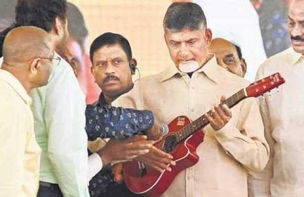 Chief Minister N Chandrababu Naidu plays on a guitar during the inauguration of Adarana-2 scheme at IGMC Stadium  in Vijayawada on Monday | P Ravindra Babu