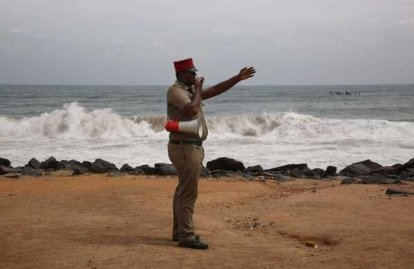 A policeman announcing over a megaphone to clear the beach area in Pondicherry as sea behaves roughly along the coast on Thurday with Cyclone 'Gaja' expected to make a landfall late in the evening. (Photo | G Pattabiraman/EPS)
