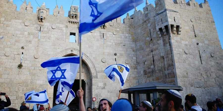 Israelis wave national flags outside the Old City's Damascus Gate, in Jerusalem. (File   AP)