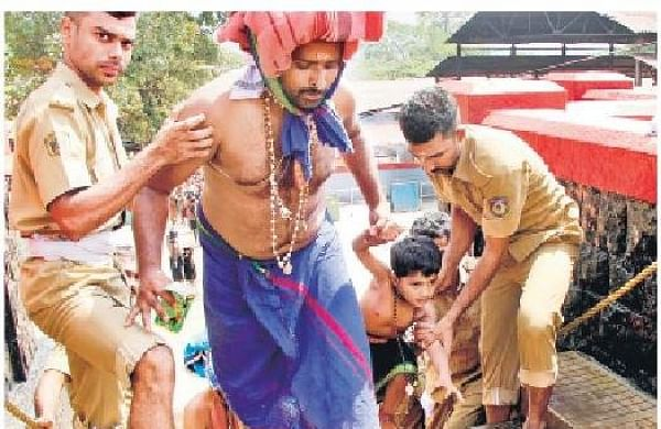 The police assist a devotee at the holy steps | Shaji Vettipuram