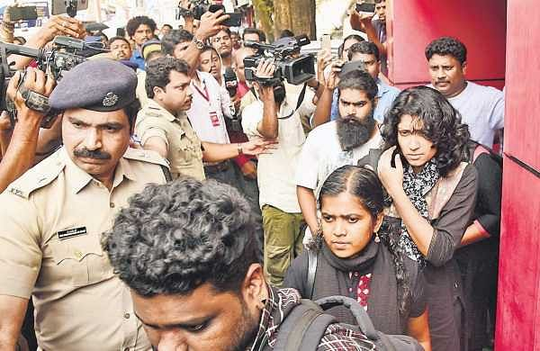 Police escort Reshma Nishant and two other women pilgrims out of the Ernakulam Press Club after they held a press meet on Monday.