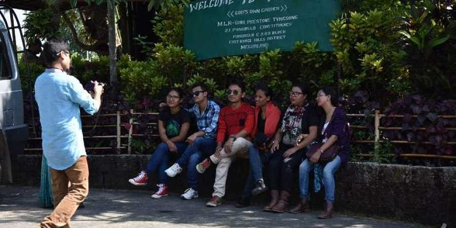 Indian tourists pose beside a sign in the village of Mawlynnong village in the north-eastern state of Meghalaya. (Photo | AFP)