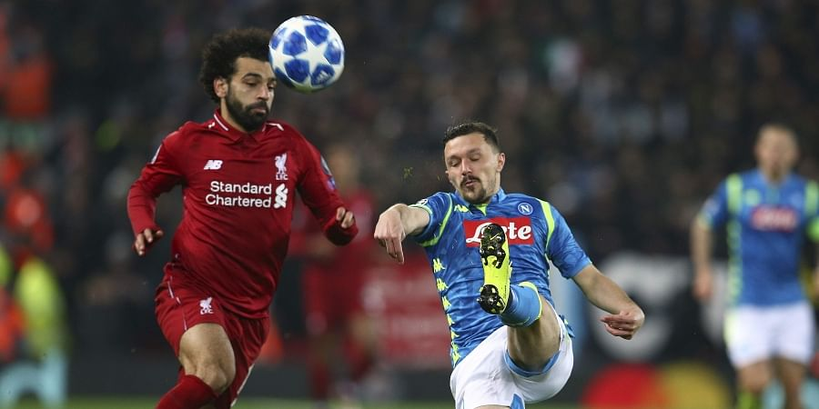 Liverpool forward Mohamed Salah, left, and Napoli defender Mario Rui challenge for the ball during the Champions League Group C soccer match between Liverpool and Napoli at Anfield stadium in Liverpool. (Photo | AP)