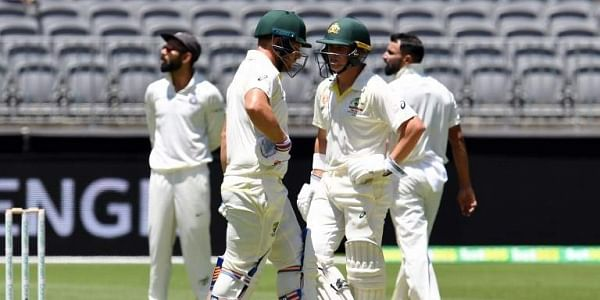 Australia's batsmen Marcus Harris (R) and Aaron Finch wait for a third umpire decision during day one of the second Test cricket match between Australia and India in Perth. (Photo   AFP)